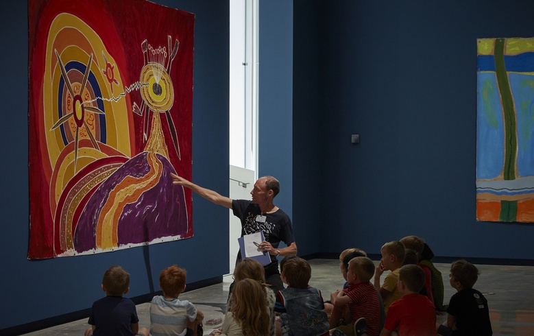 Educator Chris Barry talks with students about creation and volcanoes with Len Lye's paintings