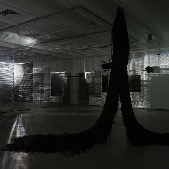 Installation view <em>Haegue Yang: Triple Vita Nestings,</em> Institute of Modern Art, Brisbane. In view (l-r): <em>Lethal Love</em>, 2008/2018, aluminium venetian blinds, powder-coated aluminium hanging structure, steel wire rope, free-standing mirror wall, moving spotlights, scent emitters (Wildflower, Gunpowder), dimensions variable; <em>The Intermediate – Tinted UHHHHH Creature Inverted V</em>, 2017, powder-coated stainless steel frame, steel wire rope, plastic twine, 360 x 400 x 180 cm, courtesy of the artist. Photo: Carl Warner