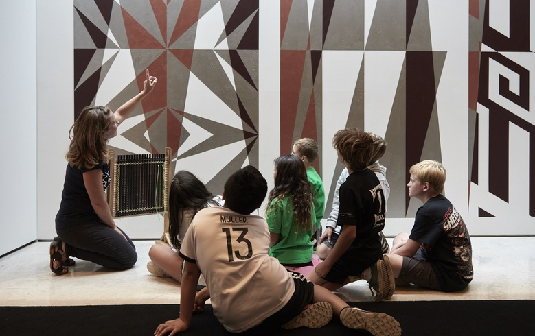 Kaiako Jess Marshall talks with students about tukutuku patterns
