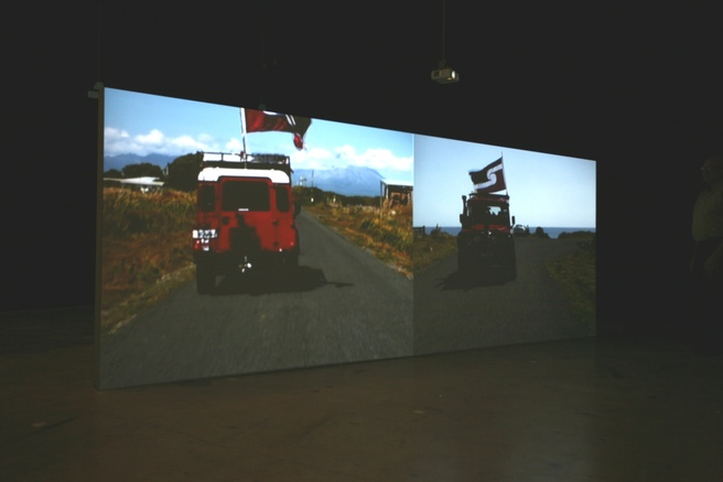 Alex Monteith <em>Parihaka to Cape Egmont Rd to Parihaka with two Tino Rangatiratanga Flags and Two Land Rovers, Waitangi Day</em> 2009. Two channel video installation with three channel audio, 18 min. Govett-Brewster Art Gallery Collection