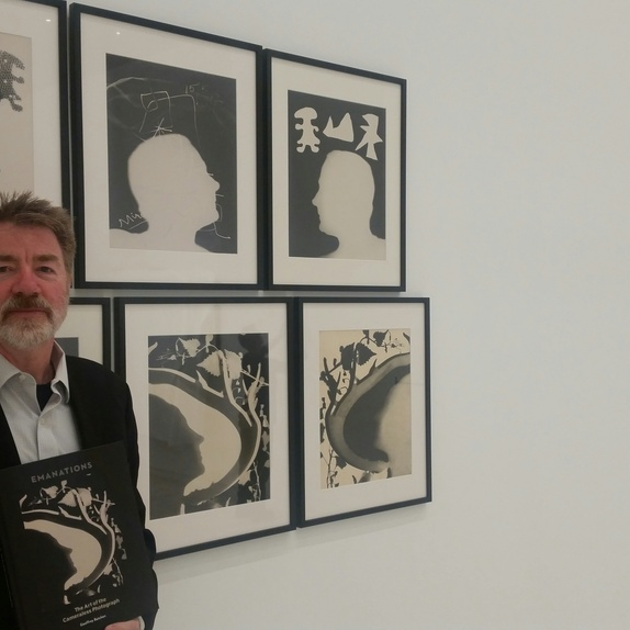 Author Geoffrey Batchen with his book and Len Lye's photograms in the exhibition <em>Emanations: The Art of the Cameraless Photograph</em>