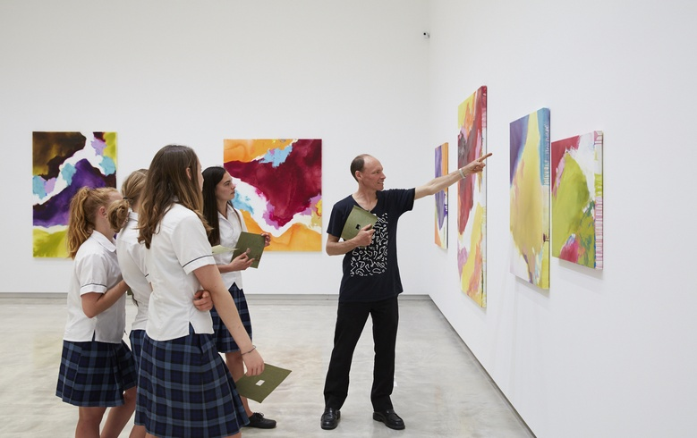 Educator Chris Barry and students with Amanda Gruenwald's paintings. Photo Sam Hartnett